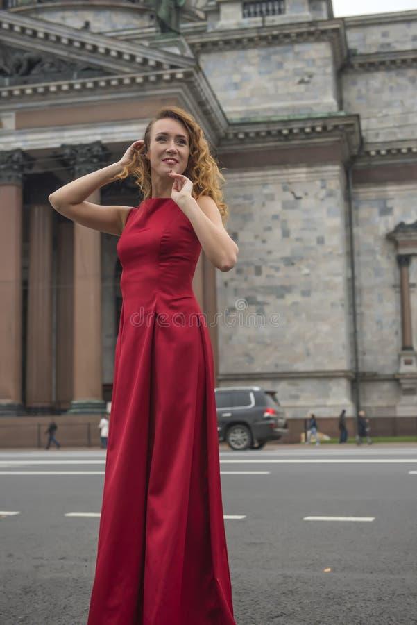 Härlig elegant kvinna i en röd klänning royaltyfri bild