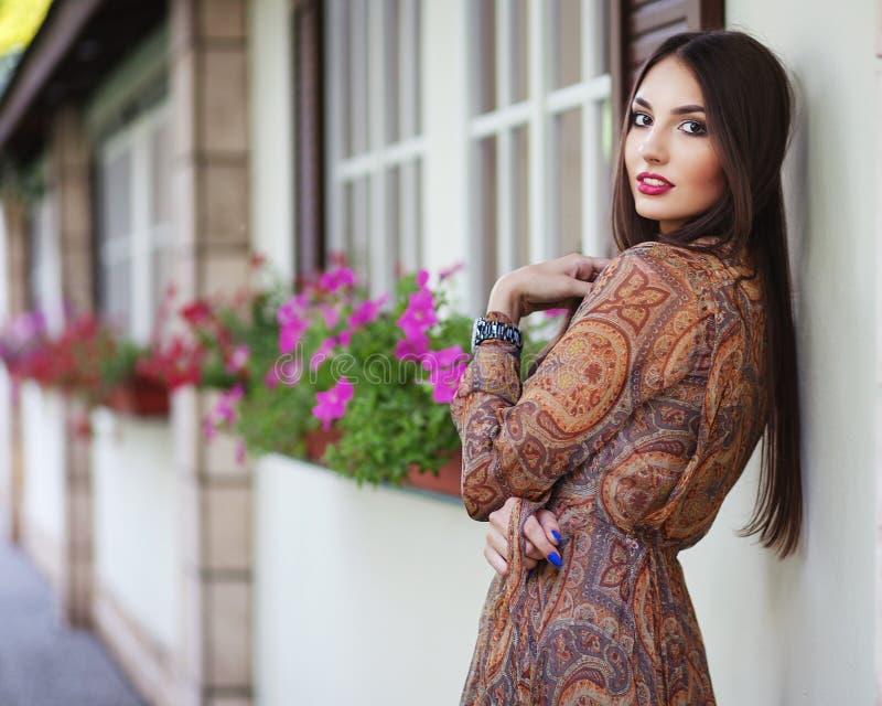 Härlig elegant kvinna i romantisk klänning över väggen med flo arkivfoton