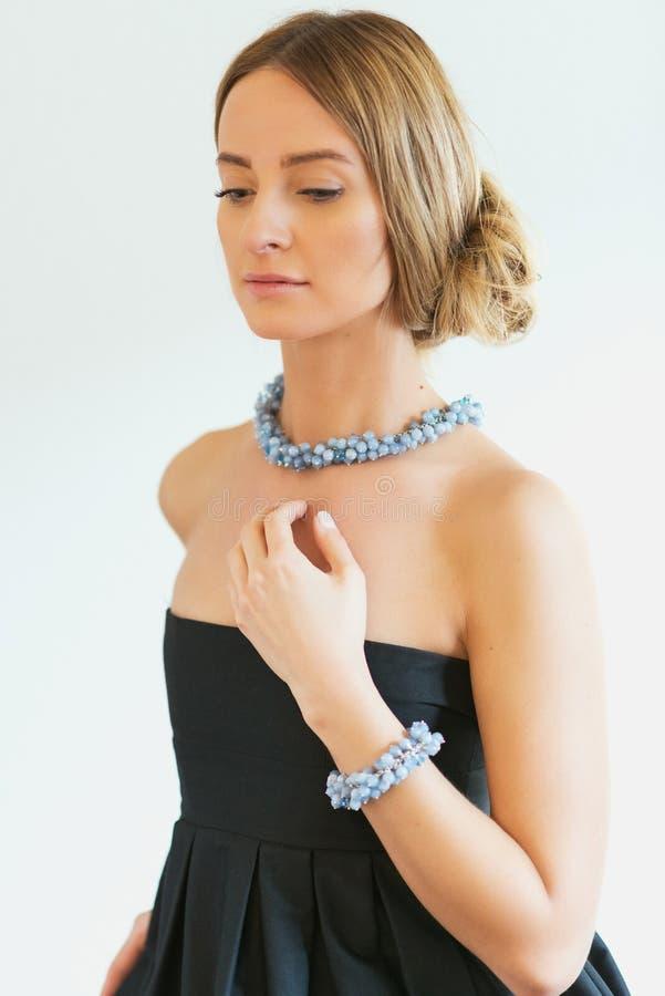 Härlig elegant kvinna i svart klänning med blåa smycken royaltyfri bild