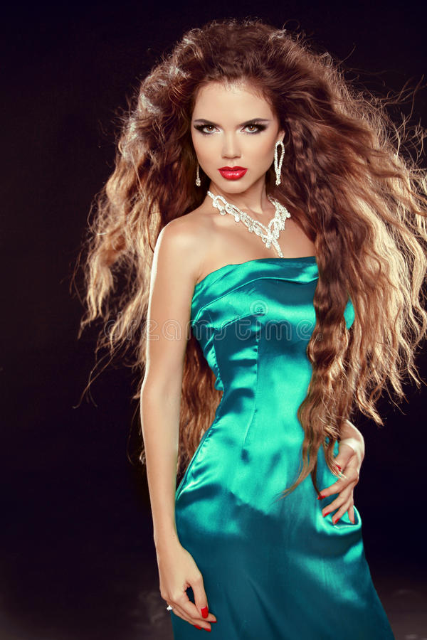 Härlig elegant kvinna med långa lockiga hår i elegant klänning  arkivfoto