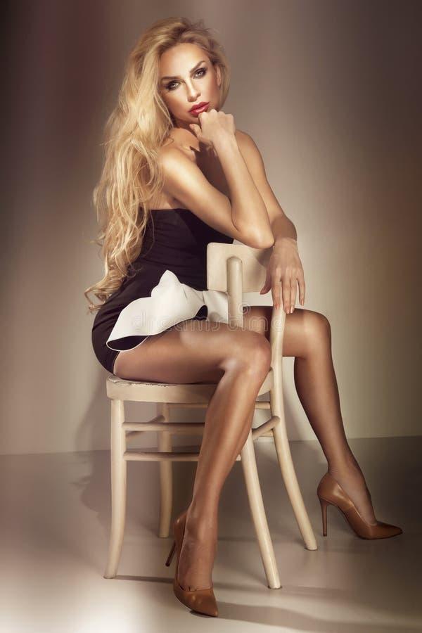 Härligt lyxigt blont kvinnasammanträde på stol. Skjuten studio. arkivfoton