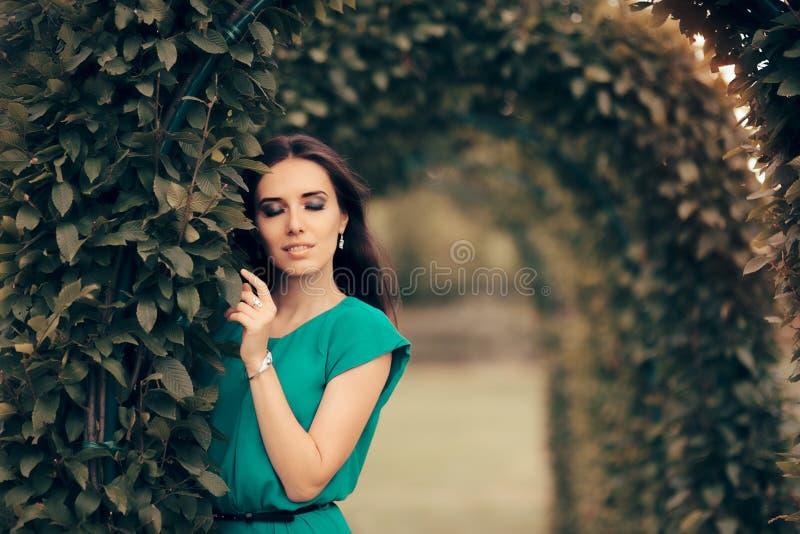 Härlig elegant kvinna som deltar i det formella partiet i trädgården arkivfoto