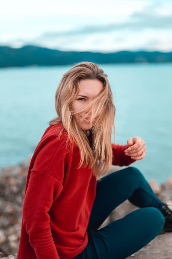 Härlig elegant sexig flicka i stor röd kall klänning, på havet royaltyfri fotografi