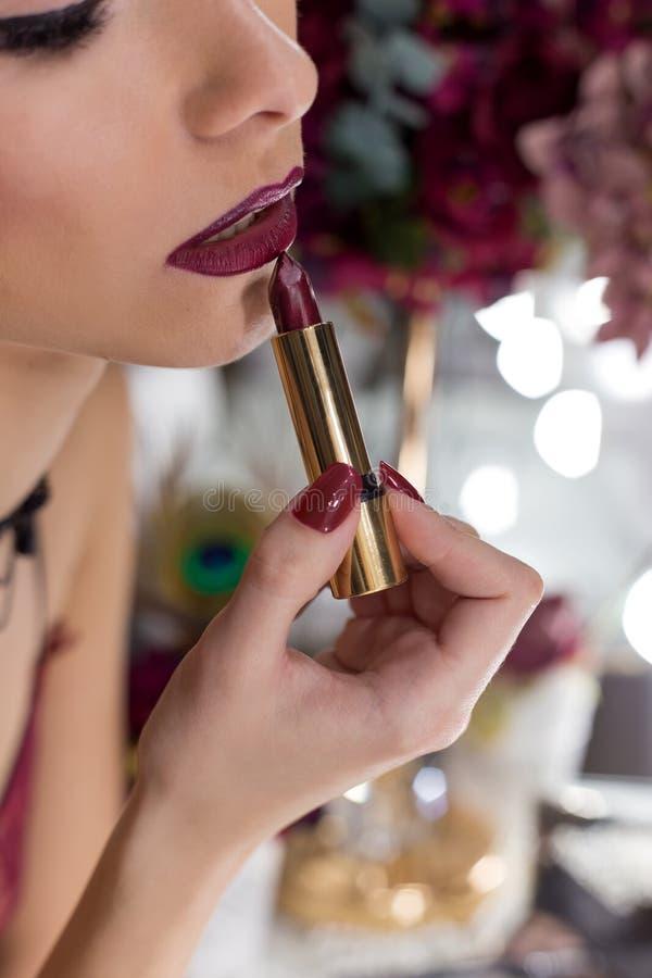 Härlig elegant sexig flicka med ljus marsala för färg för makeupläppstiftläppstift framme av spegeln i logen arkivfoton