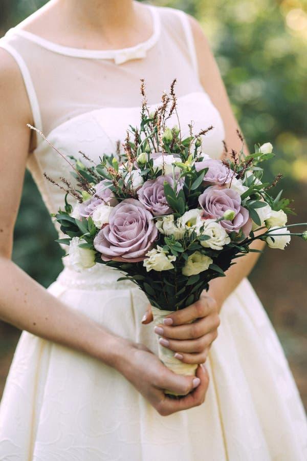 Härlig elegant sommarbröllopbukett av lila rosor och vildblommor i händerna av bruden i den vita bröllopsklänningen arkivfoton