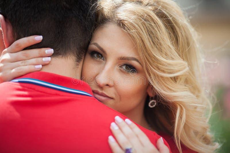 Härlig emotionell blond brud som kramar den tillfälliga brudgummen, closeup arkivfoto