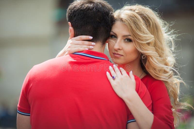 Härlig emotionell blond brud som kramar den tillfälliga brudgummen, closeup arkivfoton