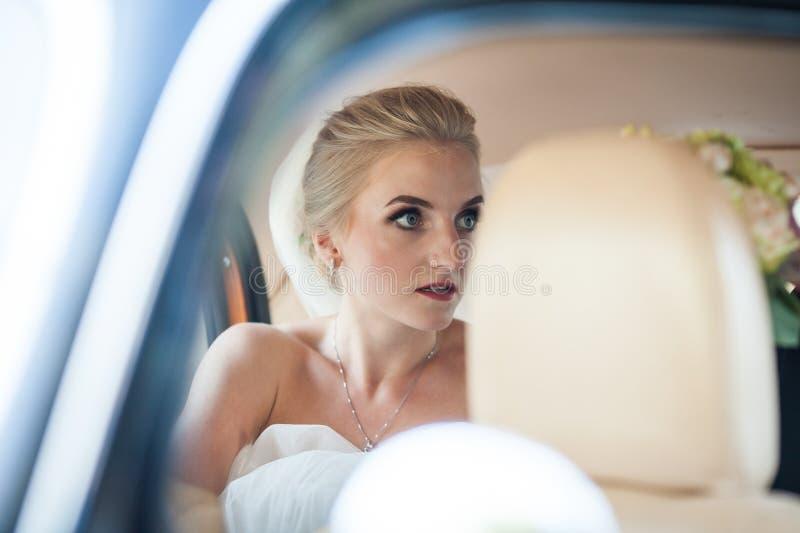 Härlig emotionell blond brud som poserar i den lyxiga bilen, framsidaclos arkivbild