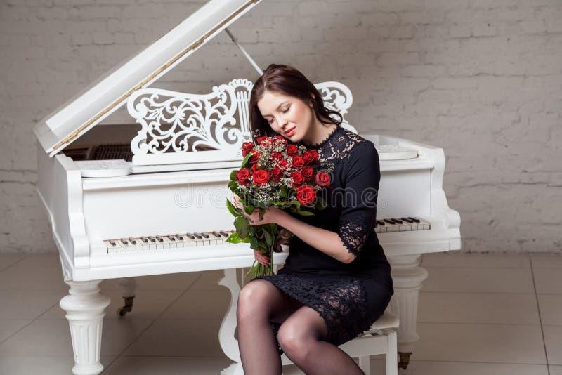 Härlig emotionell brunettkvinna i den svarta klassiska klänninginnehavbuketten av röda rosor som sitter nära piano med stängda ög royaltyfria foton