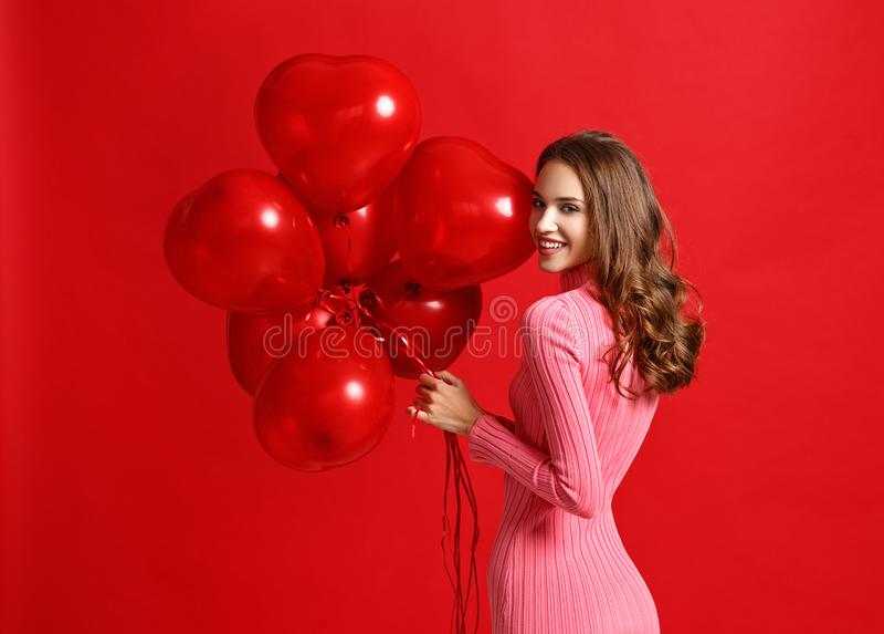 Härlig emotionell flicka i rosa klänning med röda ballons på röd bakgrund royaltyfria foton