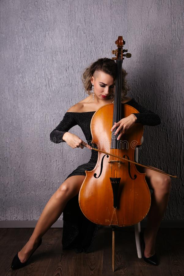 Härlig emotionell kvinna i en aftonklänning som spelar violoncellen royaltyfri fotografi