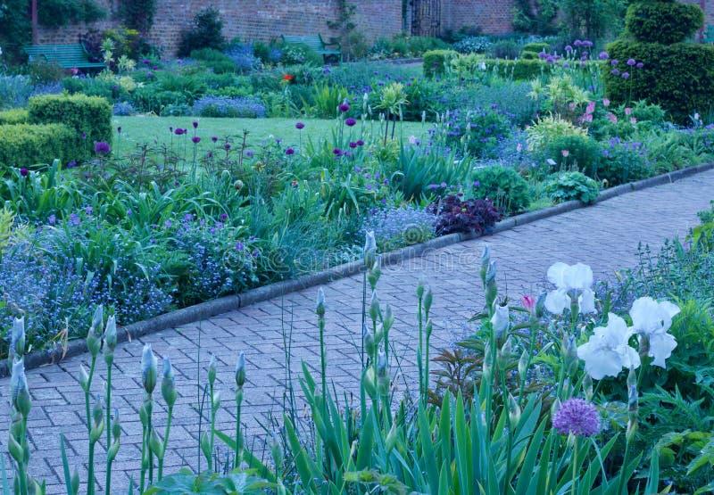 Härlig engelsk stugalandsträdgård med banan som kör mellan rabatter royaltyfri foto