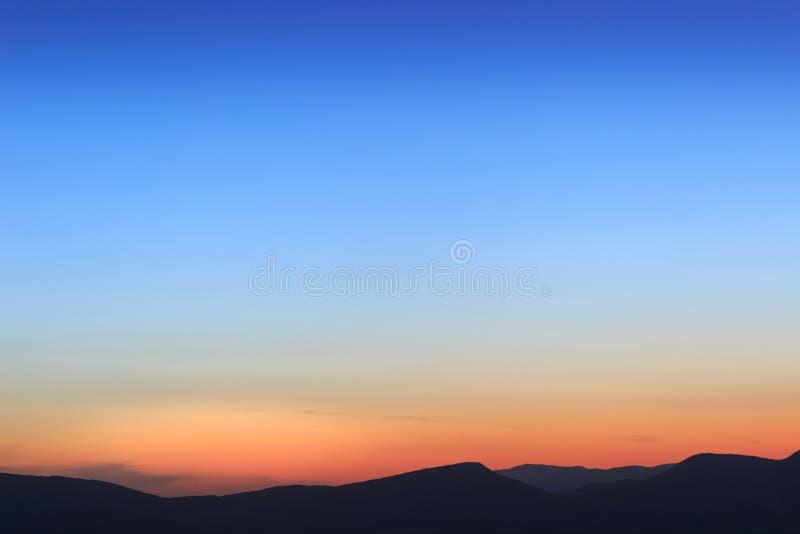 Härlig enkel djupblå och orange solnedgånghimmel arkivbild