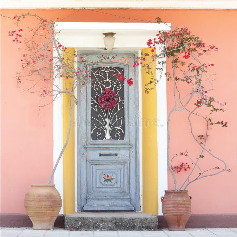 Härlig enkel husdörr med blommor arkivfoton