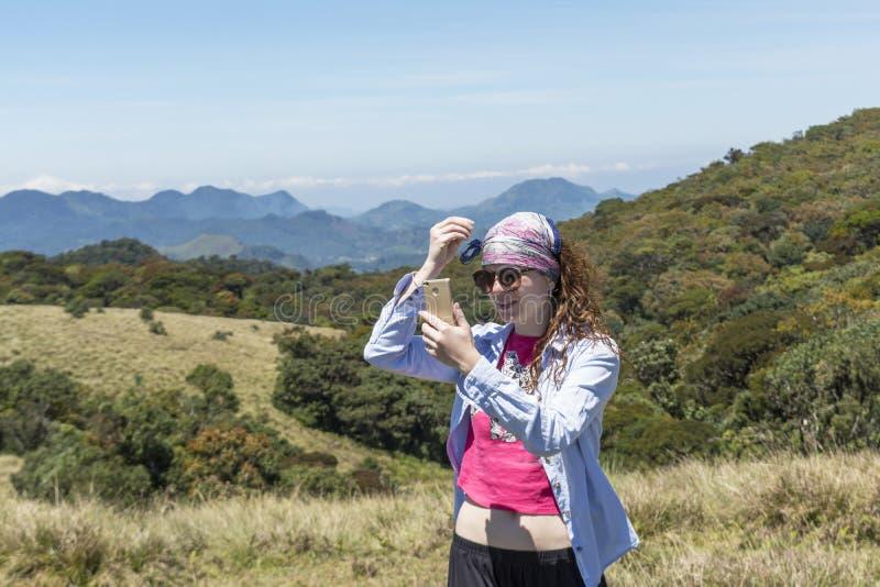 Härlig europeisk kvinna som får klar för selfiefoto nära bergen fotografering för bildbyråer