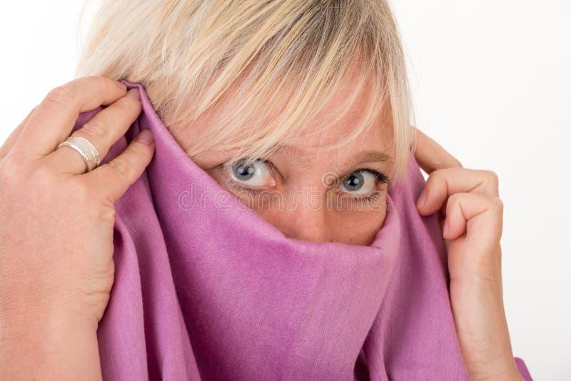 Härlig europeisk mitt- åldrig kvinna som döljer hennes framsida bak en sjal arkivbild