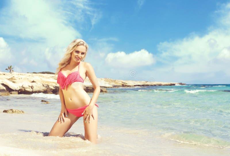 Härlig, färdig och sexig flicka i den rosa baddräkten som poserar på en strand royaltyfri bild