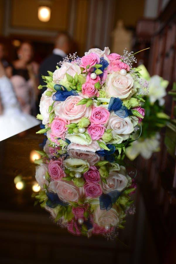 Härlig färgrik bröllopbukett med bruden och brudgummen i bet royaltyfria bilder
