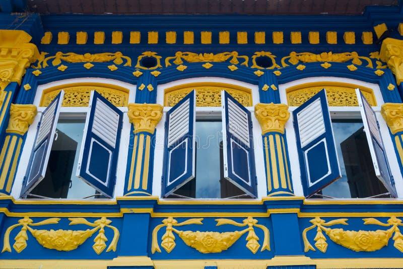 Härlig färgrik fasad med slutare för öppet fönster Härlig färgrik fasad med slutare för öppet fönster härliga singapore royaltyfri bild