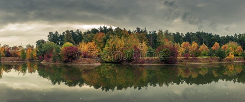 Härlig färgrik höst den pittoreska panoramautsikten av staden parkerar med mångfärgade träd reflekterade i floden i molnigt arkivfoto