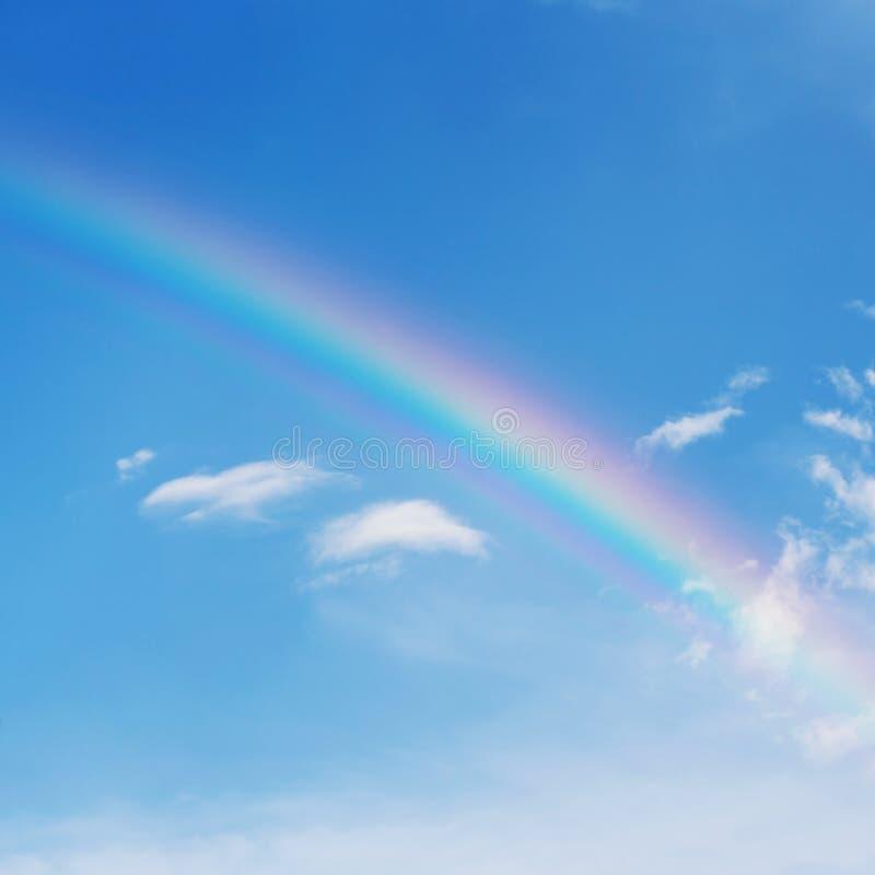Härlig färgrik regnbåge på blå himmel arkivfoton