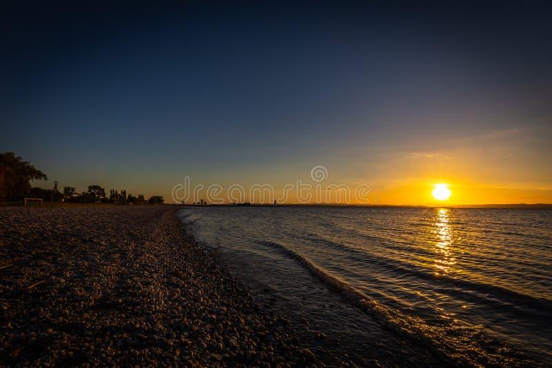 Härlig färgrik solnedgång över stranden av sjön Neusiedler i Podersdorf royaltyfria bilder