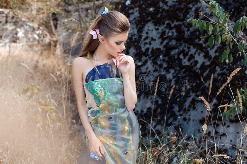 Härlig försiktig söt flicka i sagateckenet i rollen av den wood älvan som går till och med skogen med fjärilar i henne royaltyfri bild