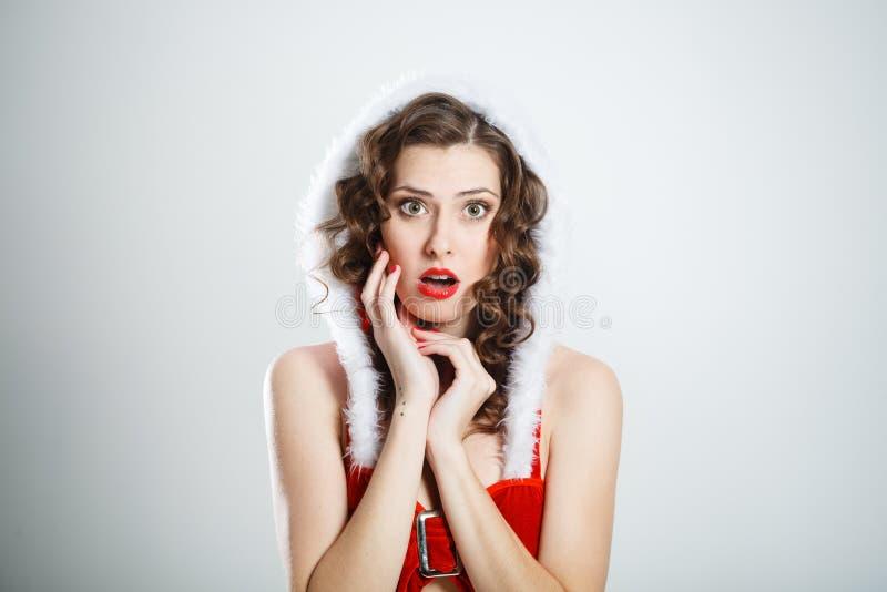 Härlig förvånad kvinna som bär Santa Claus kläder arkivbild