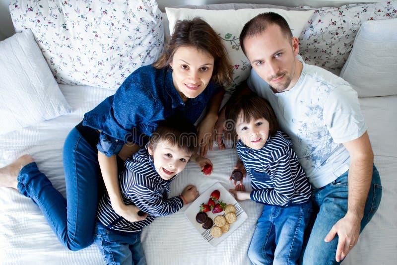 Härlig familj av fyra och att ligga på sängen som äter jordgubbar royaltyfria bilder