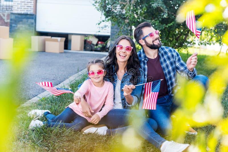 härlig familj med amerikanska flaggan och solglasögon som sitter i trädgård av royaltyfria bilder