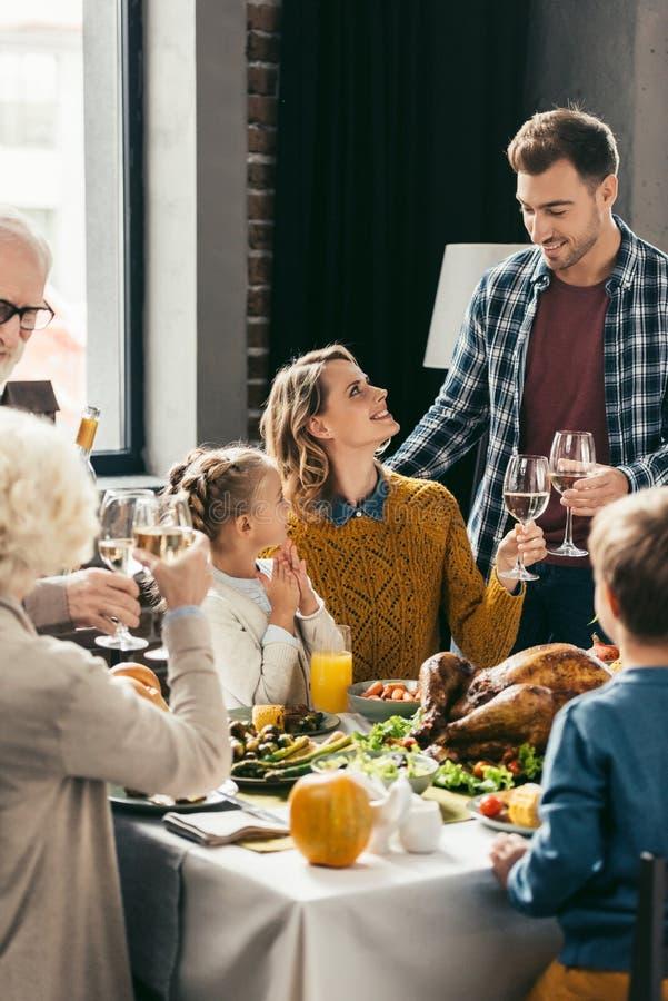 härlig familj som rostar med exponeringsglas för vitt vin fotografering för bildbyråer