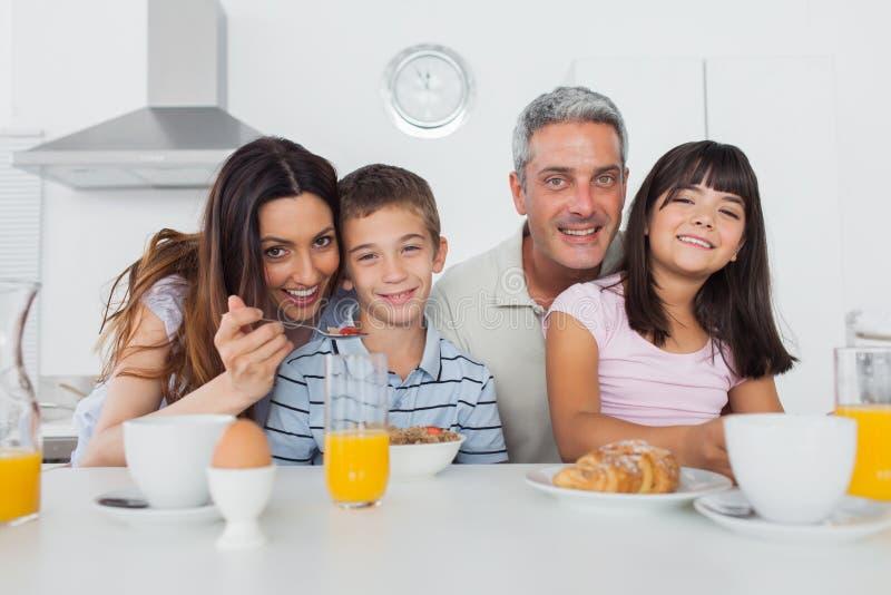 Härlig familj som tillsammans äter frukosten i kök arkivbild