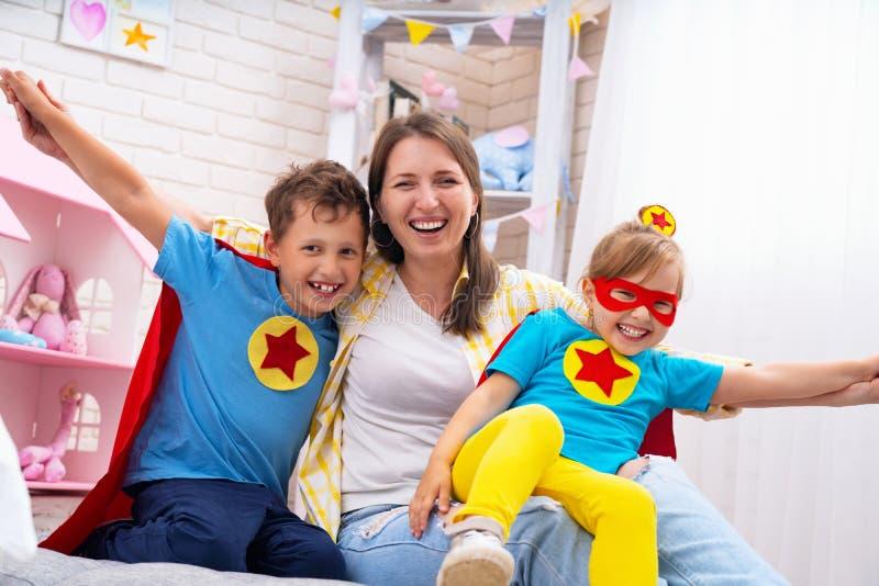 Härlig familjmamma och dotter med iklädda dräkter för son av toppna hjältar i roliga maskeringar och röda kappor att spela Begrep royaltyfri fotografi