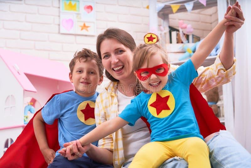 Härlig familjmamma och dotter med iklädda dräkter för son av toppna hjältar i roliga maskeringar och röda kappor att spela Begrep royaltyfria bilder