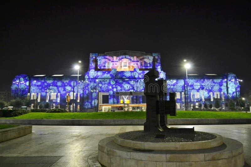 Härlig fasad av den Milan Central järnvägsstationen exponerad i blått för julferierna arkivbild