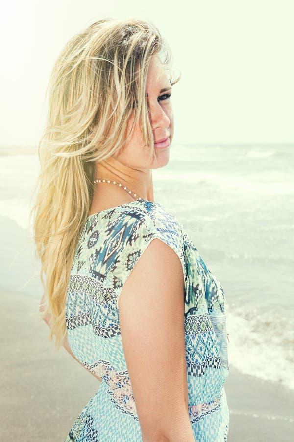 Härlig flicka för blont hår med havsbakgrund Söt inställning arkivfoto