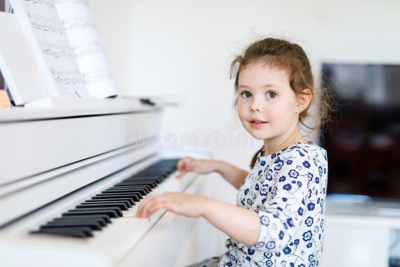 Härlig flicka för liten unge som spelar pianot i vardagsrum eller musikskola arkivbild