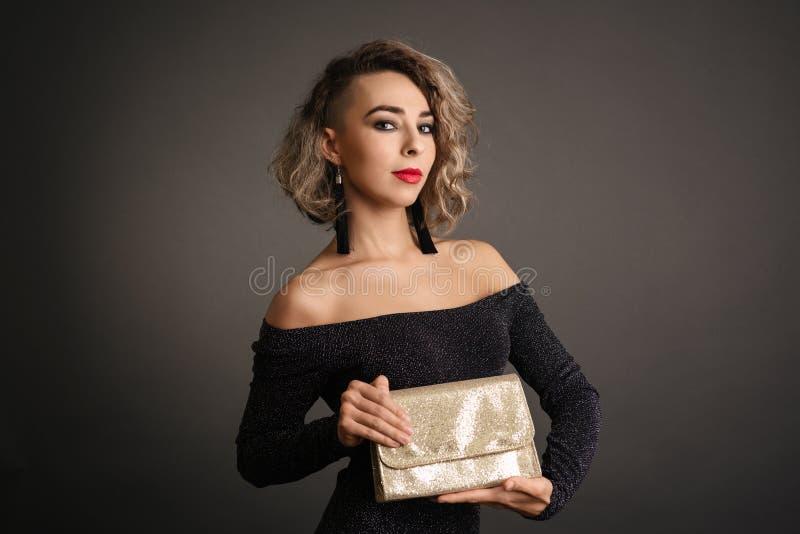 Härlig flicka för modemodell som rymmer en guld- handväska royaltyfri bild