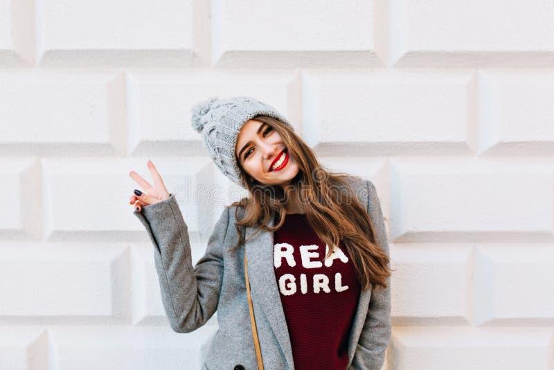 Härlig flicka för stående med långt hår och röda kanter på grå väggbakgrund Hon bär det gråa laget och den stack hatten henne royaltyfria bilder