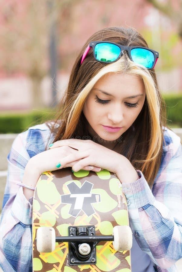 Härlig flicka för stads- stående med skateboarden som ner ser fotografering för bildbyråer