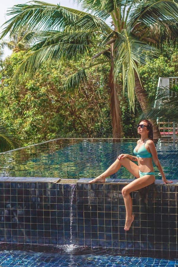 härlig flicka i bikinin som sitter på poolside arkivfoto