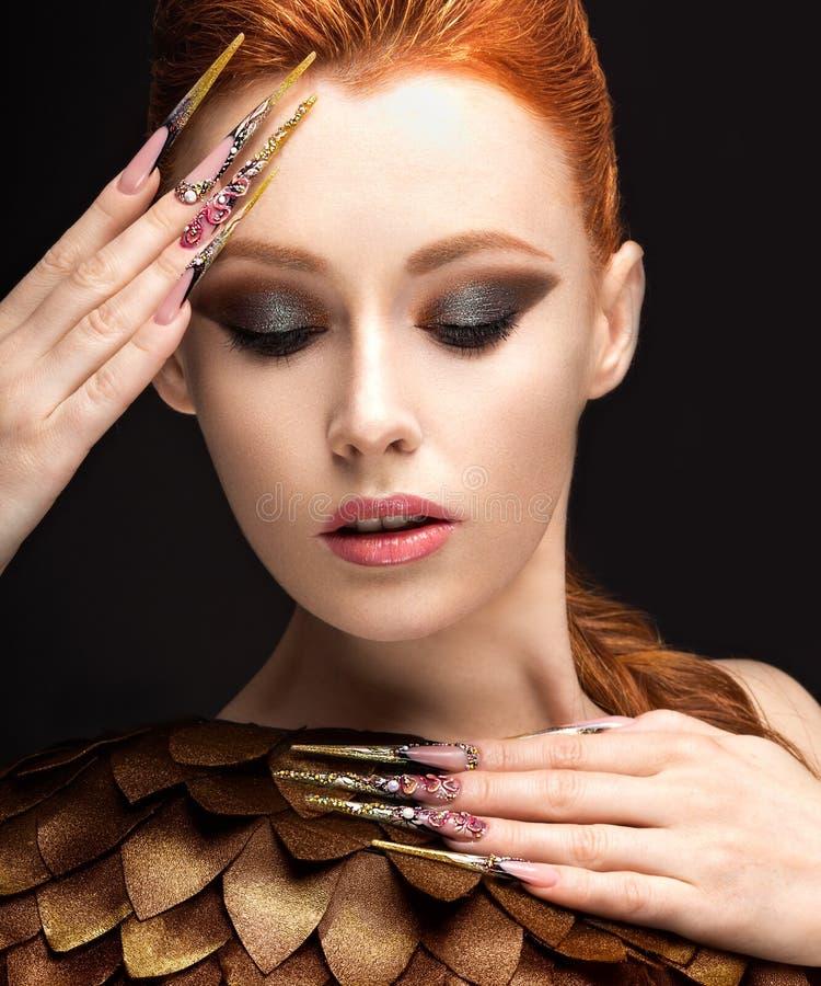 Härlig flicka i bilden av Phoenixen med ljus makeup, långa fingernaglar och rött hår Härlig le flicka arkivbilder