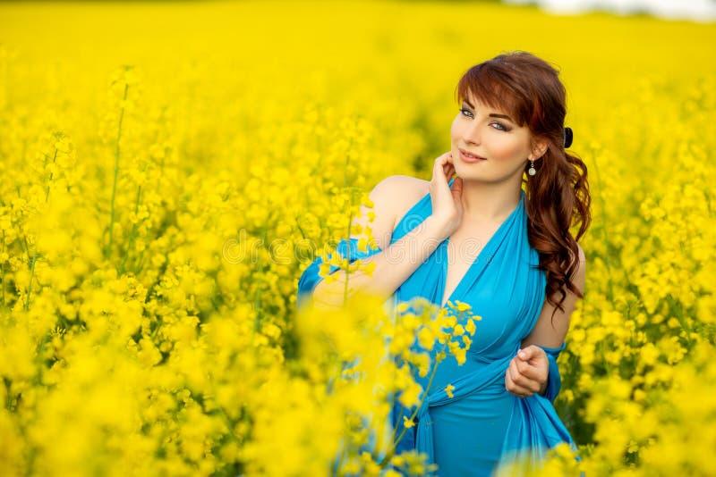 Härlig flicka i blå klänning med gula blommor royaltyfria foton