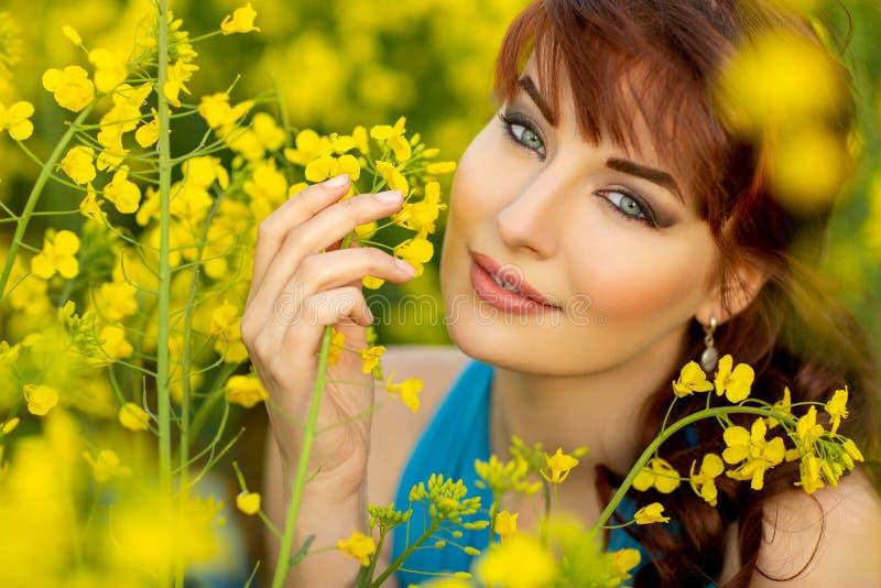 Härlig flicka i blå klänning med gula blommor royaltyfria bilder