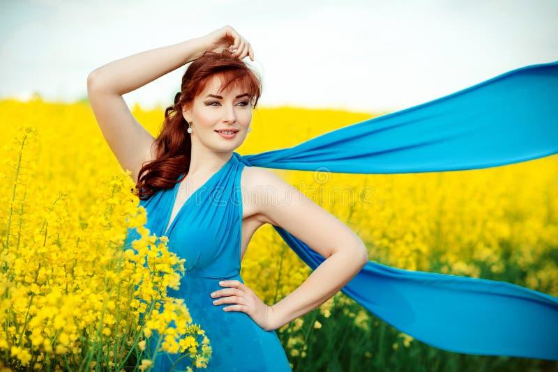 Härlig flicka i blå klänning med gula blommor royaltyfri fotografi