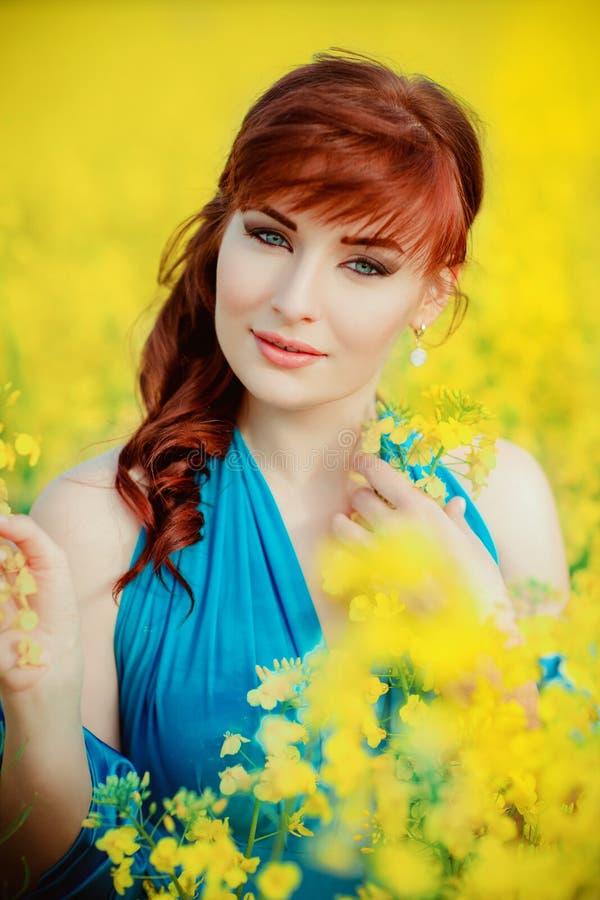 Härlig flicka i blå klänning med gula blommor royaltyfri bild
