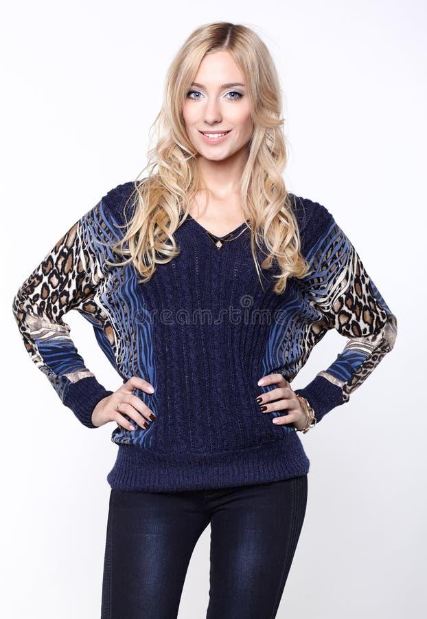 Härlig flicka i blå tröja och jeans arkivfoto