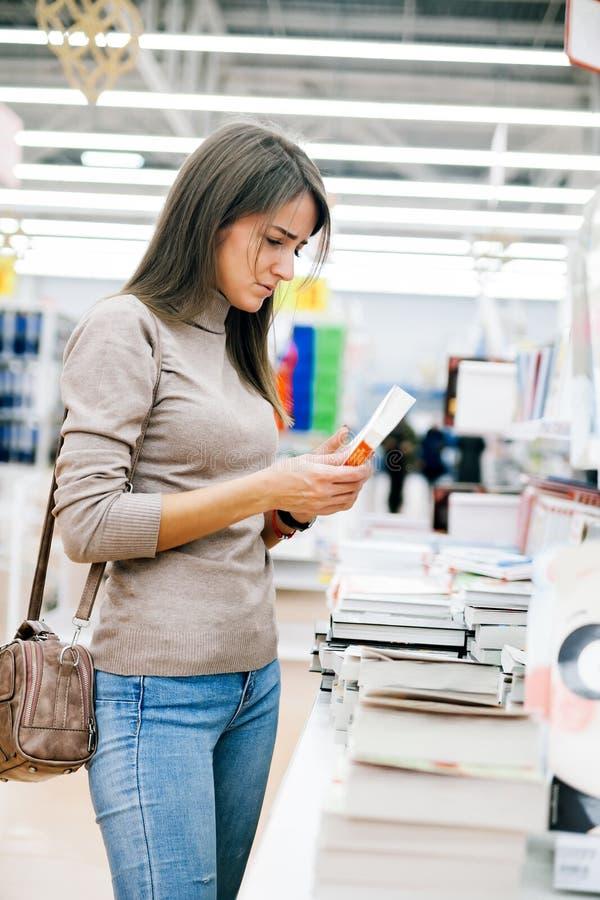 Härlig flicka i bokhandel fotografering för bildbyråer