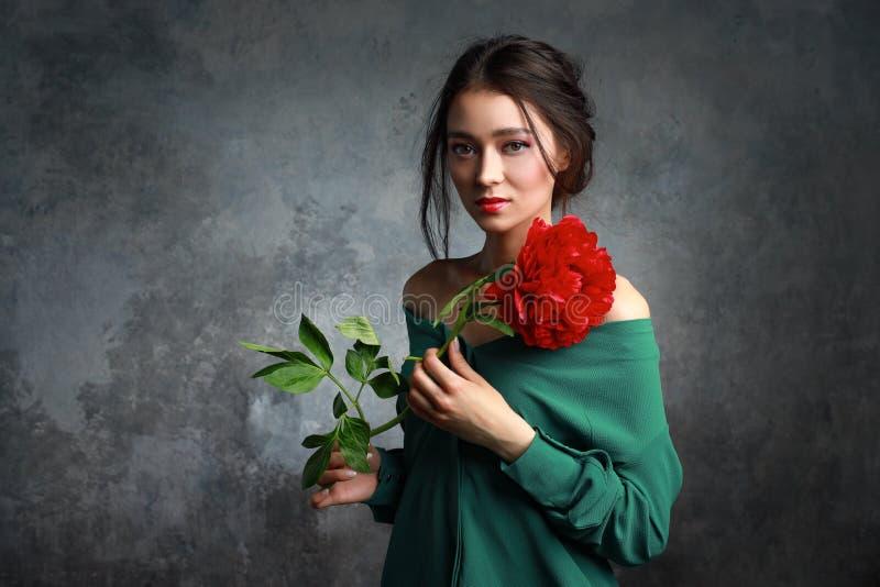 Härlig flicka i den gröna klänningen med blommapioner i händer på ett ljust - grå bakgrund Glad asiatisk kvinnlig modell som in p royaltyfria foton