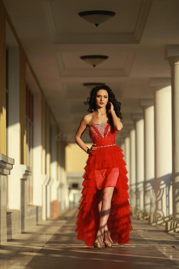 Härlig flicka i den röda klänningen utomhus på bakgrunden av kolonner royaltyfri fotografi